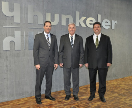 Franz Hunkeler (center) stands with his sons Stefan (right) and Michel (left) in front of the newly constructed extension for the Hunkeler Group's Production division. Together, the two brothers hold 100 percent of the share capital.