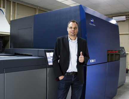 Arndt Eschenlohr, president of PLS Print Logistic Services Germany GmbH, stands in front of the KM-1 press.