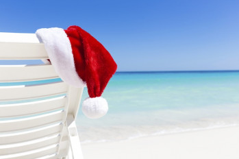 Santa Claus Hat on sunbed near sandy beach with turquoise caribbean sea water. Tropical Christmas Card