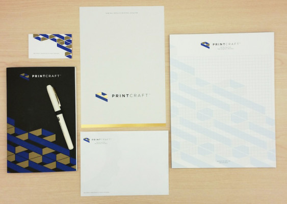 Displayed here are the six components in the folder — a business card, notepad, notebook, pen, card, and an envelope that displays the company's name and logo.