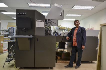 Bharat Mehta, Triaz Digital Printing president, stands with the company's new Scodix S digital enhancement press.