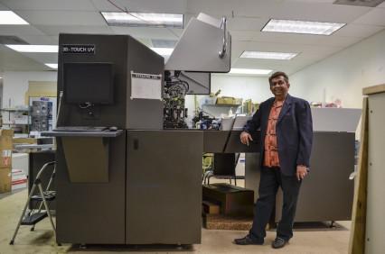 Bharat Mehta, Triaz Digital Printing president, stands with the company's new Scodix S digital enhancement press.