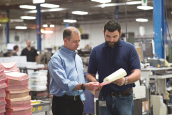 DFS President Fred Collins, shown left, and a shop floor employee carefully inspect the job specifications on an incoming Web-to-print order.