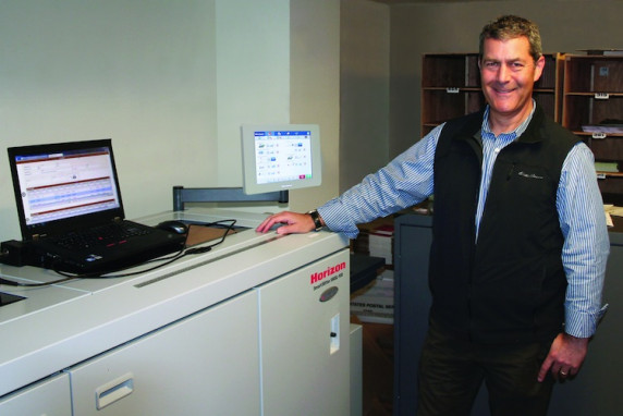 Chuck Stempler, president of AlphaGraphics, stands with his company's newly installed SmartSlitter from Standard Finishing Systems.