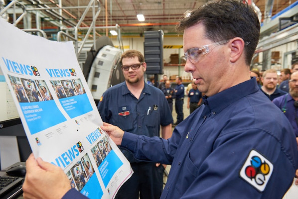 Governor Walker inspects digitally printed pages featuring a welcome message and photos from past visits to Quad/Graphics facilities.