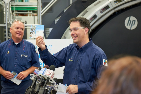 Governor Walker is holding up a personalized postcard printed at the company's Midwest Digital Print Supercenter. The postcard features a picture of the governor snapped minutes earlier.