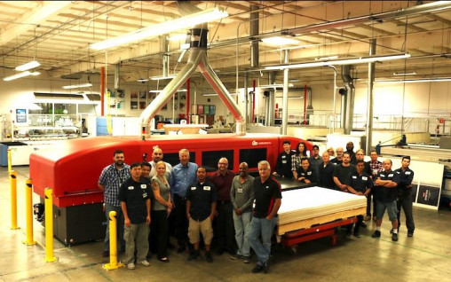 Dome executives Tim Poole (sixth from left) and Bob Poole (eighth from left) stand with employees in front of their newly installed EFI VUTEk HS125 Pro inkjet press.