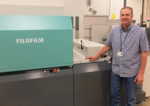 Brian Tilot stands with Independent Printing's new J Press 720S from Fujifilm.