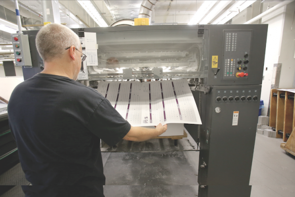 CIA Imaging & Publishing Support uses a five-color, 40˝ manroland offset press with a coater to print its long-run products. Here, a press operator pulls a sample from the delivery end of the press.