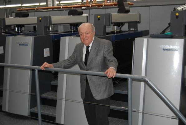 Julius Miller, the founder of Rex 3, stands in front of the Heidelberg Speedmaster XL 106.