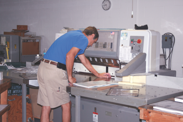 Intech Printing's Mike Pepin aligns paper on a Polar cutter.