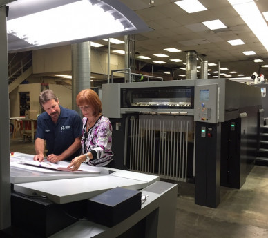 Wayne Yeager, pressman; and Kathy Atkins, president/CEO, of Riegel Communications, review a proof printed on the Speedmaster XL 106-6+L.