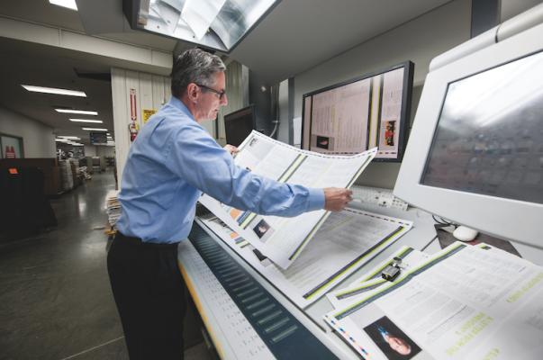 Jim Tomblinson, VP of operations, performs a press check for the Heidelberg Speedmaster XL 105 press.
