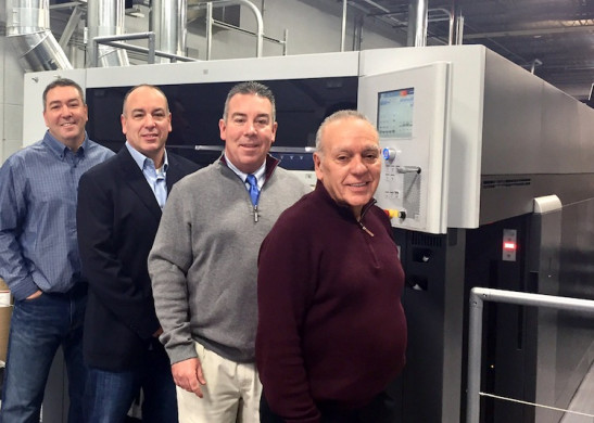 The staff at Paulson Press stand next to the company's newly installed Speedmaster XL 106-4+LYY-P+4+L with UV from Heidelberg.
