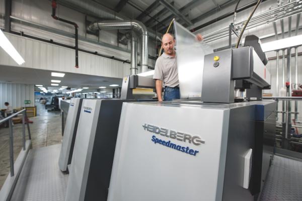 Pressman Brandon Bailey conducts a plate change on the new 10-color Heidelberg Speedmaster XL 106 perfector.