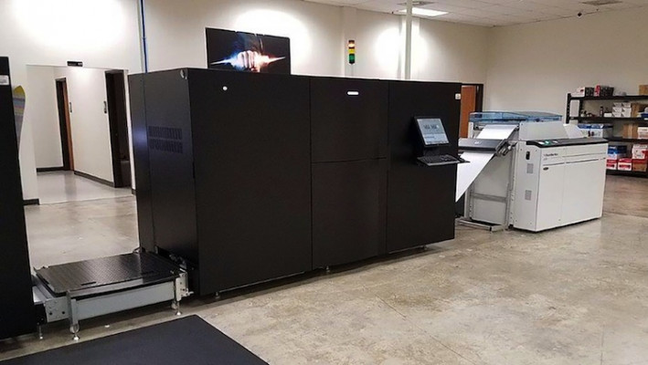 Pictured here is the Standard Hunkeler UW6 unwinder and one of the engines of the continuous-feed Ricoh InfoPrint 5000 GP color inkjet press in operation at NMD&D Inc.