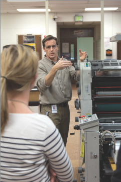 Michael Born introduces students to the Ryobi 3302H printing press.