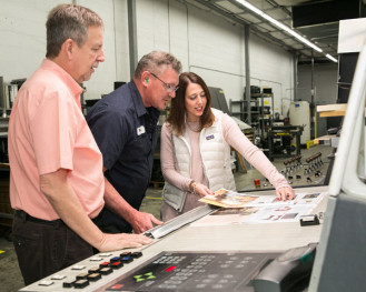 From left) Donnie Burrell, director of operations (Jacksonville Division); Vergil Backes, pressman; and Christa Nuckols, director of account managers, review a press sheet from a five-color M110 heatset web offset press.