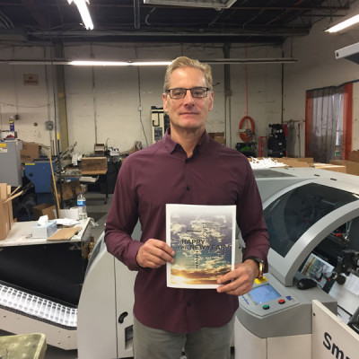 John Patrick Publishing Co. CEO John Hartmann holds up a proof that was printed on an HP T Series PageWide inkjet web press and then finished near-line on JPPC's IBIS Smart-binder SB-3 Plus HS saddle stitcher (in background).