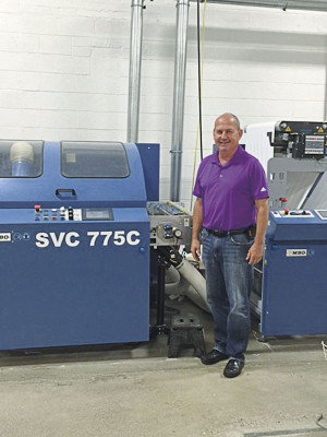 Allied Printing COO Tony Pelc stands next to the 30˝ SVC 775 C sheeter that is part of the SHP 800 high-pile stacking system from MBO America. The finishing equipment from MBO runs near-line to Allied's HP PageWide T300 inkjet web press.