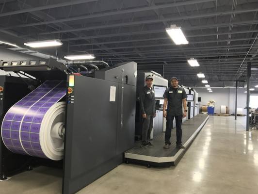 Two pressmen stand next to Digital Lizard's HP Indigo 50000 digital press.