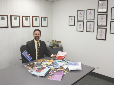 President Steve Johnson shows off clients' digital books and publications in Copresco's trophy room of awards and honors.