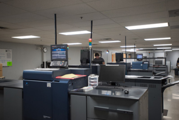 Operator Justin Czemierys stands inside the Hartland, Wis., plant's cut-sheet digital color room, which is equipped with nine high-speed Konica Minolta digital printers.