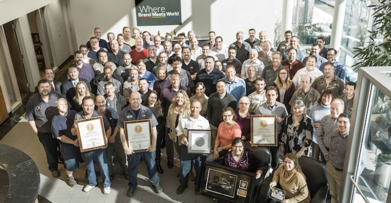 First-shift and office personnel proudly display some of the awards LCP received for its high-quality printing capabilities.