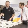 Grand-Format Head Operator Dillon Hodgden (left) and Pete Douglas inspect a job printed on the EFI VUTEk 3250 printer.
