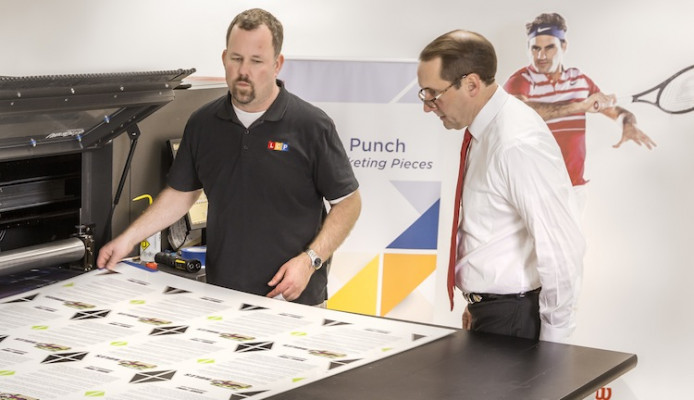 Grand-Format Head Operator Dillon Hodgden (left) and Pete Douglas inspect a job printed on the EFI VUTEk 3250 printer.