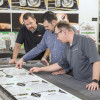 Pictured above, from the left, LCP employees Dillon Hodgden, Garrett Kasselder and Mark Goecke review Dibond sheets that are being cut on an MCT Digital flatbed router/cutter.