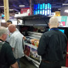 Attendees at the ISA Expo visit the EFI booth to see the new EFI Pro 16h wide-format hybrid roll/flatbed LED printer.