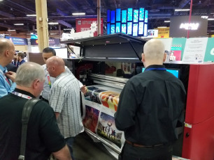 Attendees at the ISA Expo visit the EFI booth to see the new EFI Pro 16h wide-format hybrid roll/flatbed LED printer.