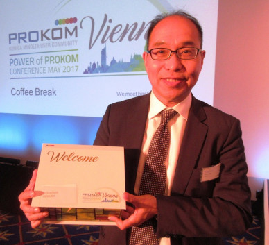 Toshi Uemura of Konica Minolta with the box for the PROKOM welcome package.
