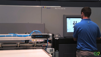 An operator stands at the consul of the Durst Rho P10 250 HS printer.