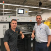 Industry Innovation in Action: Premier Printing's Tom Bennett (left) stands with press operator Peter Wlock in front of their latest LED-UV curing system install.