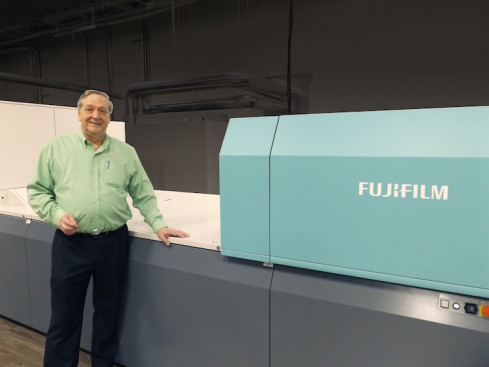 Raymond Ballew, VP of Administration, Floor Productions, proudly stands next to Fujifilm's J Press 720S, at their Dalton, Ga., facility.