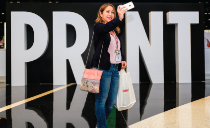 "Getting right into the spirit of PRINT 17, Benilde Banda takes advantage of the welcoming photo op, becoming the ""I"" in PRINT. She traveled from Monterrey, Mexico to view first-hand the show's latest advancements in graphic arts technology."
