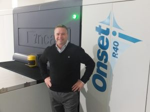 John Schiele, president, Schiele Group, stands next to the company's Onset R40i wide-format, flatbed UV press.