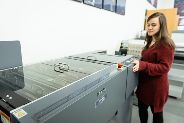 Miranda Roy, digital print technician, oversees Jet Mail Services' Duplo digital finishing system, which was also one of the recent investments that the company made.
