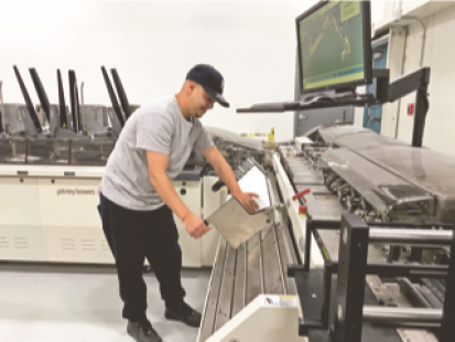 Edwin Burgos, mail department apprentice, loads envelopes on Allied Printing Services' new Pitney Bowes MPS inserter.