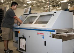 Printing Jeovani Perea, folder operator apprentice, operates a Standard Horizon BQ-270V perfect binder).jpg