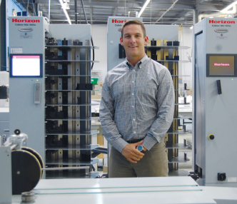 Bill Duerr, Hatteras president, stands in front of his company's Standard Horizon VAC-1000 air suction collator.