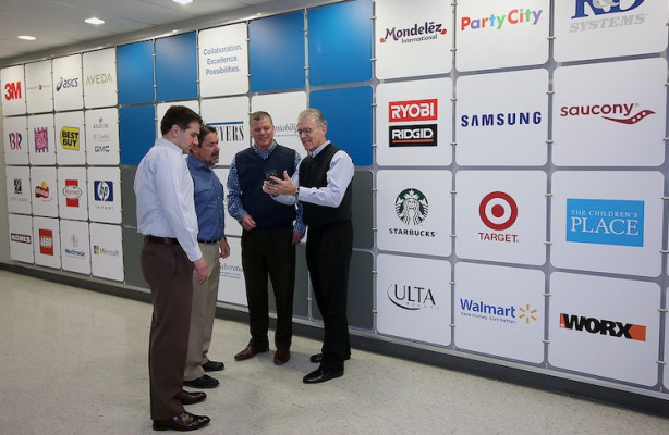 From the left, Christopher Dillon, VP of manufacturing, retail marketing solutions; Dave McConnon, VP of manufacturing, Label and Card; Glenn Brown, VP creative director; and Mike Lane, CEO; stand in the hallway at Meyers that showcases some of Meyers' clients.