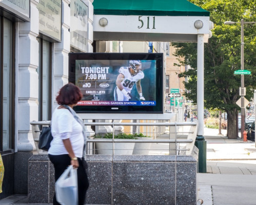 A passerby looks at the display promoting the Philadelphia Eagles on a digital urban panel.
