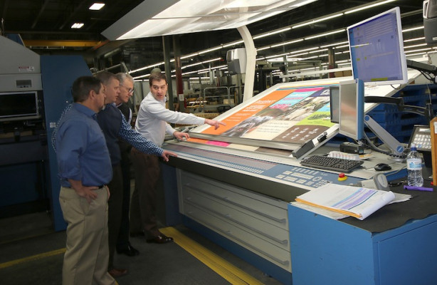 Pictured, from the left, are Dave McConnon, VP of manufacturing, Label and Card; Glenn Brown, VP creative director; Mike Lane, CEO; and Christopher Dillon, VP of manufacturing, retail marketing solutions looking at a proof that was printed on an 81˝ KBA press.