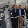 """From the left, Bill Duerr, president, and Charlie Duerr, owner/founder, stand next to Hatteras' new Speedmaster XL 106-4+LYY-P+L with """"Push-to-Stop"""" technology from Heidelberg."""