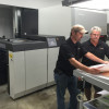 Short-Run Success-Worth Higgins & Associates production team members Butch Kelly and Ray Hairfield discuss a job in front of the company's Komori Impremia IS29 sheetfed UV inkjet press.