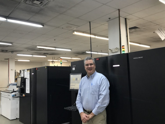 Short-Run Success-Book and journal printing takes place on a Ricoh InfoPrint 5000 continuous-feed inkjet press at Yurchak Printing. Shown with the device is John W. Yurchak, president.
