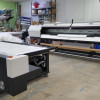 A full view of the Mimaki UJV55-320 roll-to-roll printer to the left.